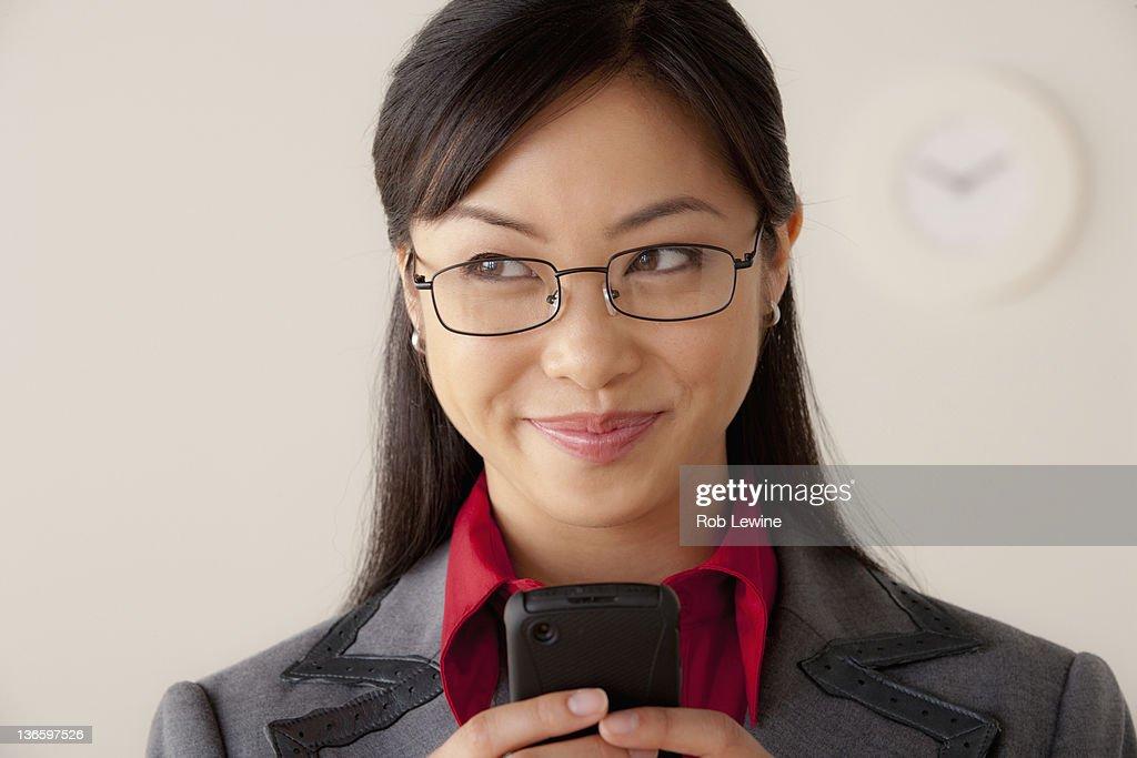 Studio portrait of businesswoman text-messaging : Stock Photo