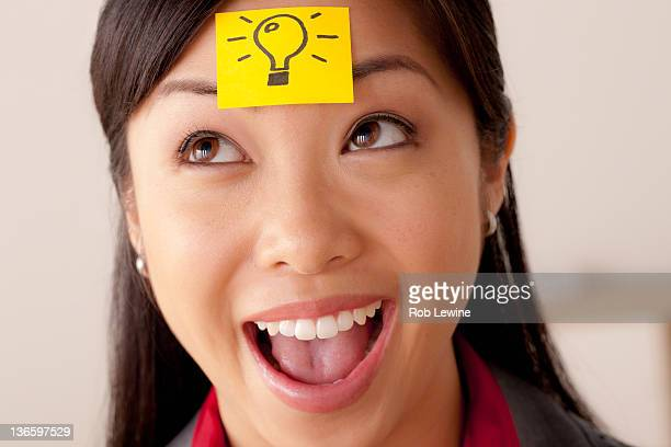Studio portrait of businesswoman with adhesive note on forehead