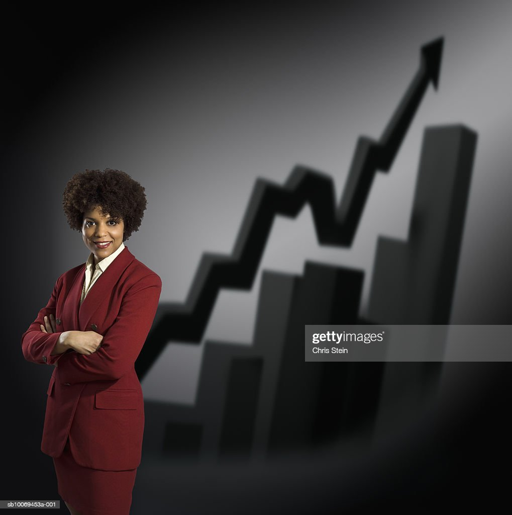 Studio portrait of businesswoman with graphs behind : Stock Photo