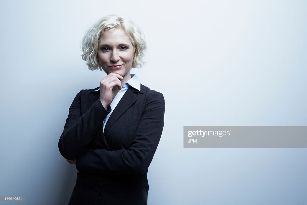 Studio portrait of businesswoman with hand on chin : Stock Photo