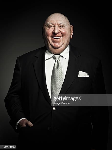 Studio portrait of cheerful senior man laughing