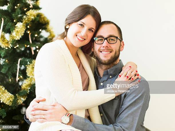 Studio portrait of couple embracing in front of Christmas tree