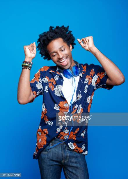 studio portrait of dancing young man in hawaiian shirt - summer stock pictures, royalty-free photos & images