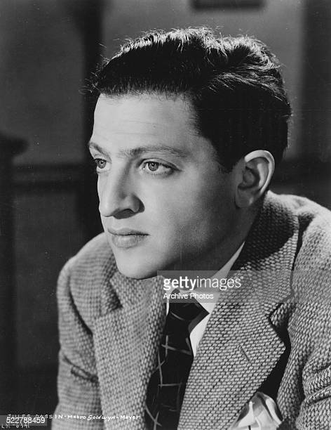 Studio portrait of director Jules Dassin wearing a suit and tie for MGM Studios circa 1945