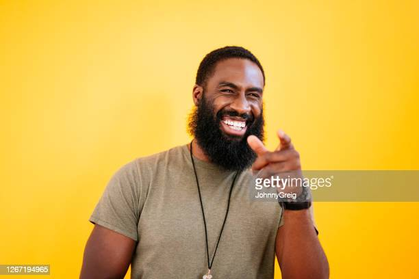 studio portrait of early 30s black man laughing and pointing - humour stock pictures, royalty-free photos & images