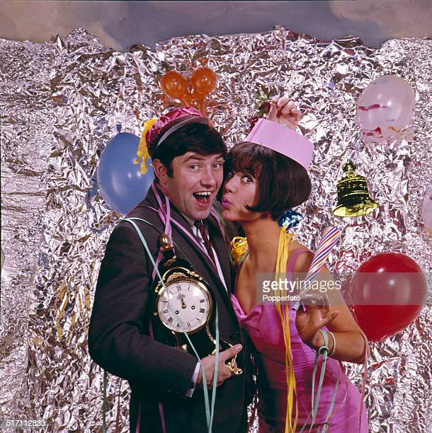Studio portrait of English comedian Jimmy Tarbuck and actress Amanda Barrie dressed to celebrate New Year's Eve at a party in 1964