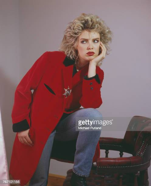 Studio portrait of English pop singer Kim Wilde posed wearing a red teddy boy style drape jacket in London in May 1985