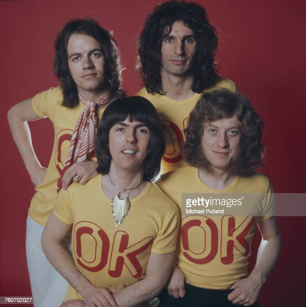 Studio portrait of English rock group Slade posing wearing tshirts with the slogan 'OK' London 1974 Clockwise from front left guitarist Dave Hill...