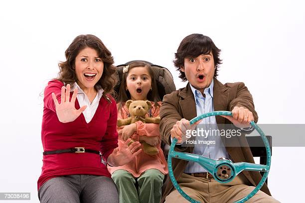 Studio portrait of family in imaginary car about to have an accident
