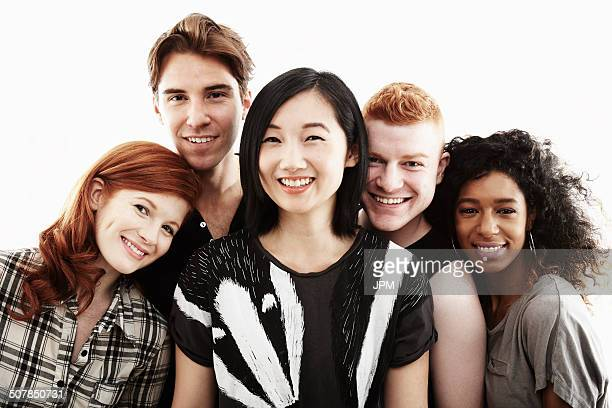 Studio portrait of five young adults smiling