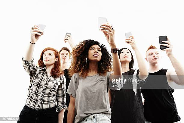 Studio portrait of five young adults taking selfies on smartphones