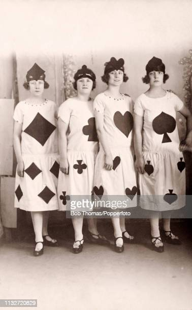 A studio portrait of four young women with varying expressions each dressed as a suit in a deck of cards left to right diamonds clubs hearts and...