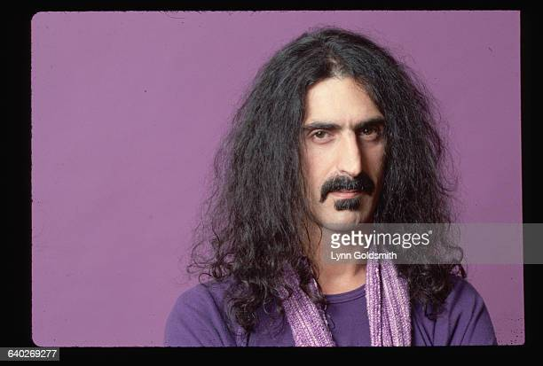 Studio portrait of Frank Zappa He is shown in a headandshoulders view against a purple background