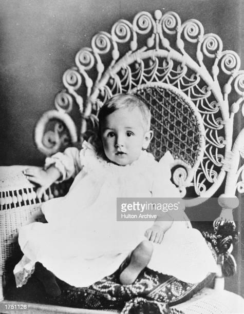 Studio portrait of future American film studio head Walt Disney as an infant seated on an ornate chair circa 1902