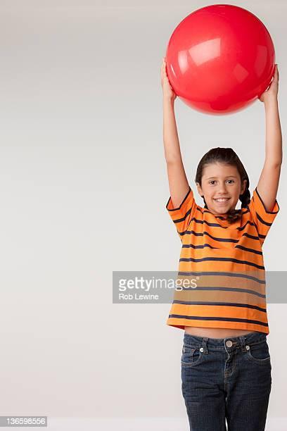 Studio portrait of girl (8-9) holding red ball