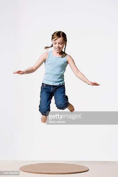 Studio portrait of girl (8-9) jumping