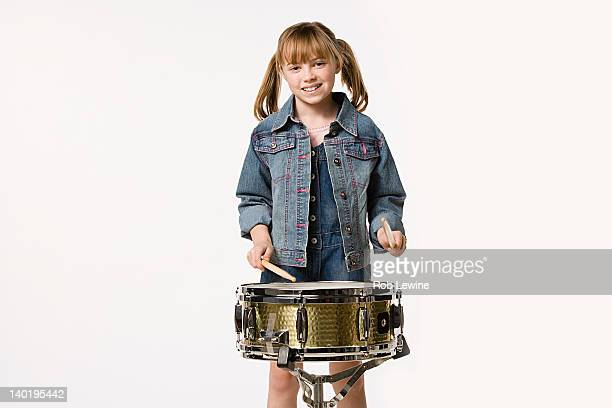Studio portrait of girl (8-9) playing drums