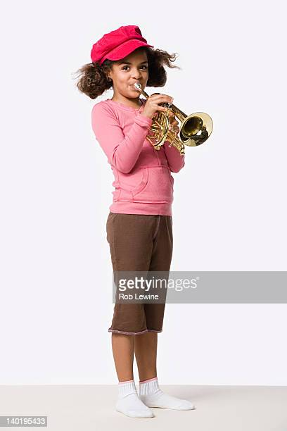 Studio portrait of girl (8-9) playing trumpet