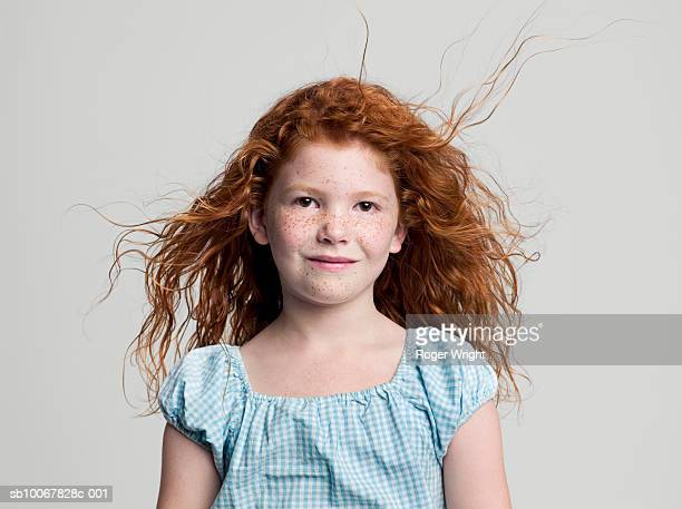 Studio portrait of girl (8-9 years) with red hair