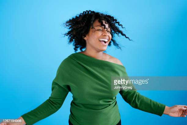 studio portrait of happy 29 year old black woman dancing - mid length hair stock pictures, royalty-free photos & images