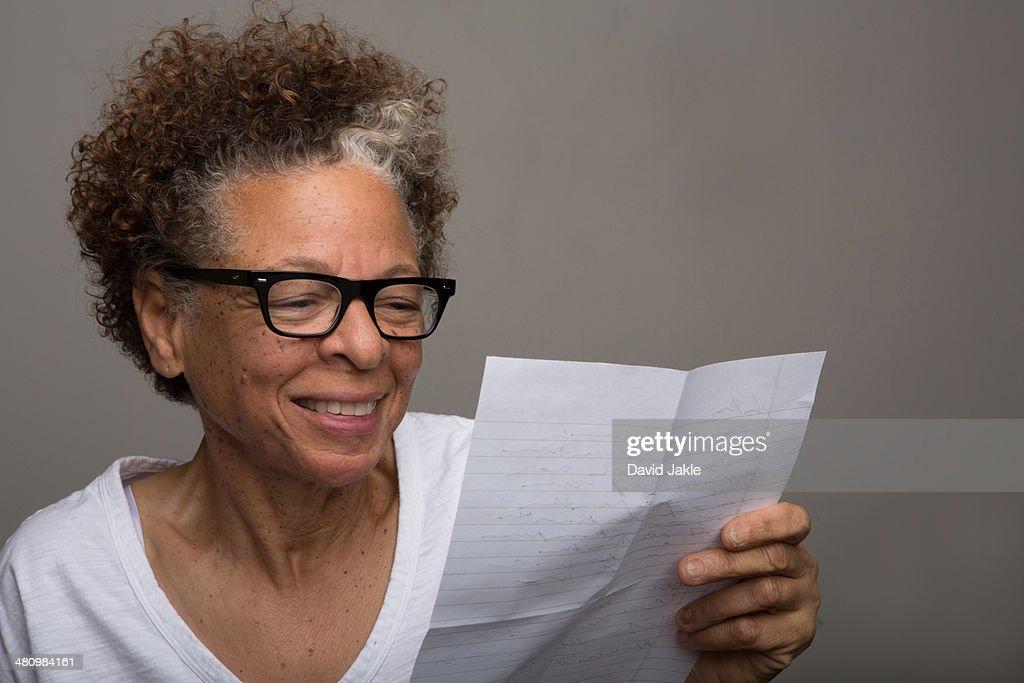 Studio portrait of happy senior woman reading a letter : Stock Photo