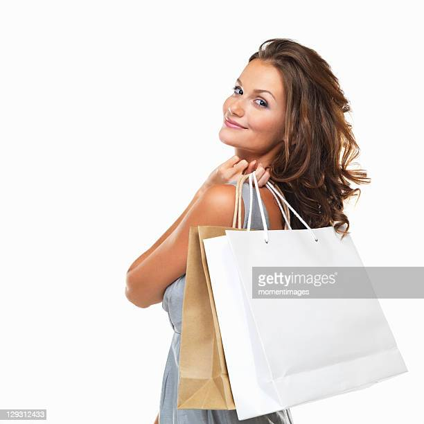 Studio portrait of happy woman holding shopping bags and looking over her shoulder