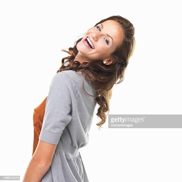 studio portrait of happy young woman looking over shoulder and smiling - looking over shoulder ストックフォトと画像