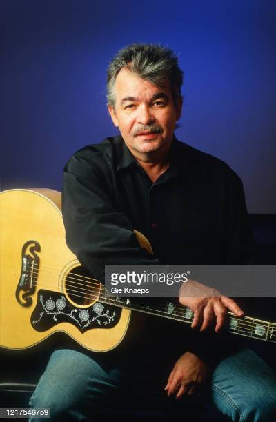 Studio portrait of John Prine posing with a Gibson J200 acoustic guitar backstage at Luna Theater Brussels Belgium 28th May 1996