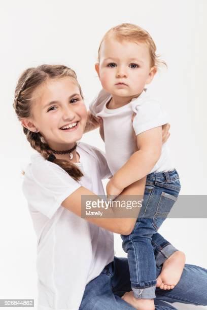 Studio portrait of kneeling girl holding baby brother