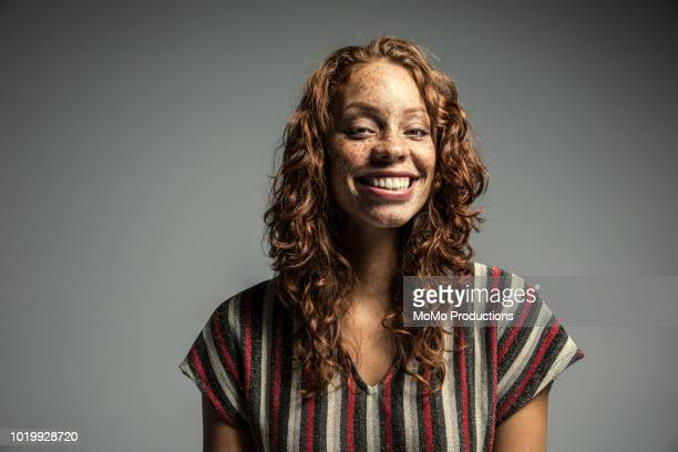 Studio portrait of laughing woman with freckles