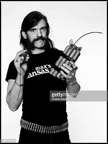 Studio portrait of Lemmy Kilmister from English hard rock band Motorhead holding sticks of dynamite and wearing a 'Max's Kansas City' tshirt London...