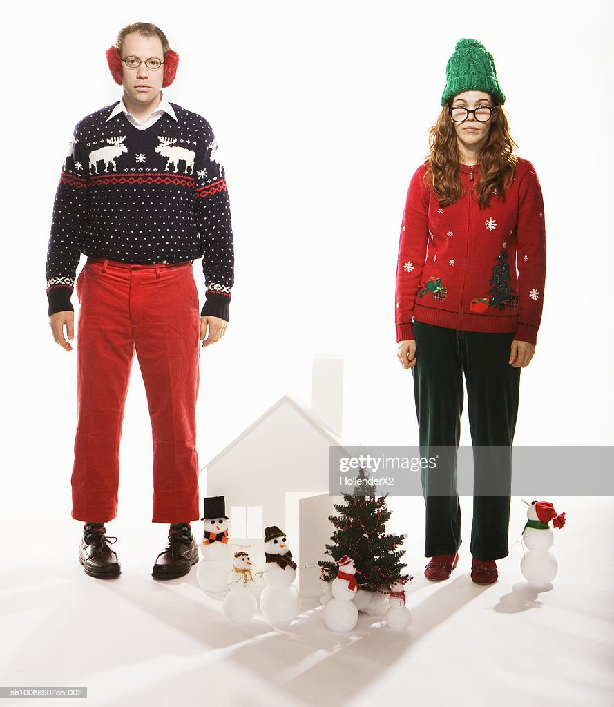 Studio portrait of man and woman in holiday sweaters with Christmas set : Stock Photo