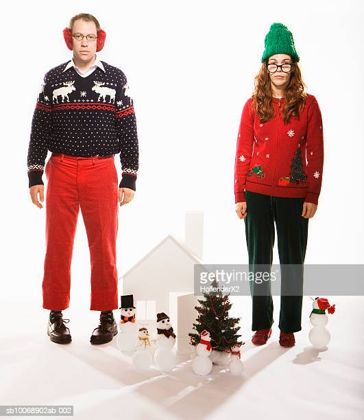 Studio portrait of man and woman in holiday sweaters with Christmas set
