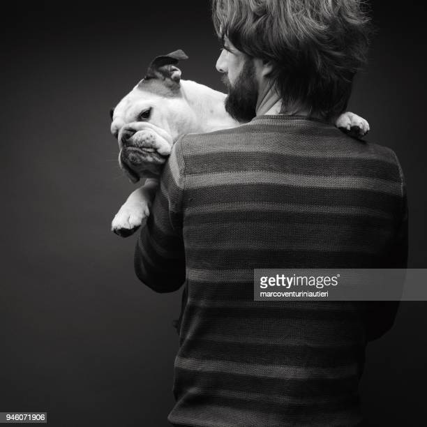 Studio portrait of man embracing his dog
