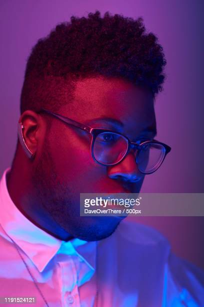 studio portrait of man illuminated by red and blue light, toronto, canada - images stock pictures, royalty-free photos & images