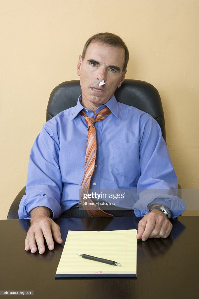 Studio portrait of man with bloody nose sitting behind desk : Stockfoto