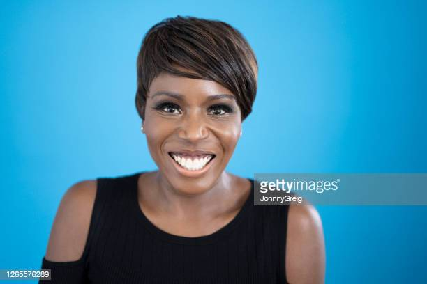 studio portrait of mature black woman smiling at camera - sleeveless stock pictures, royalty-free photos & images