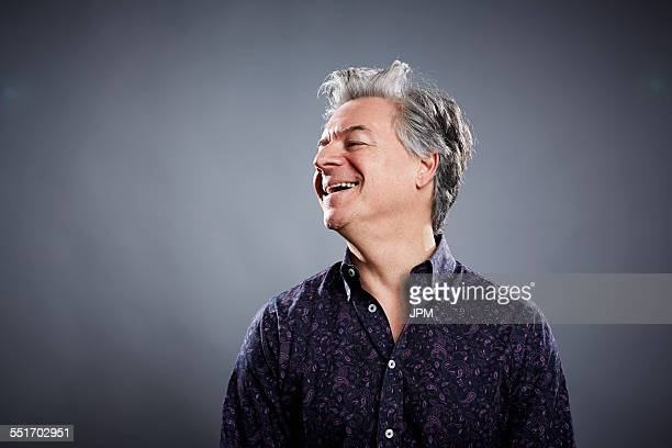 Studio portrait of mature businessman laughing