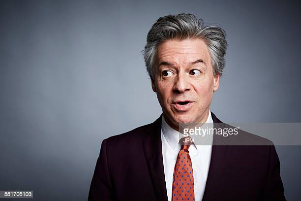 Studio portrait of mature businessman looking sideways