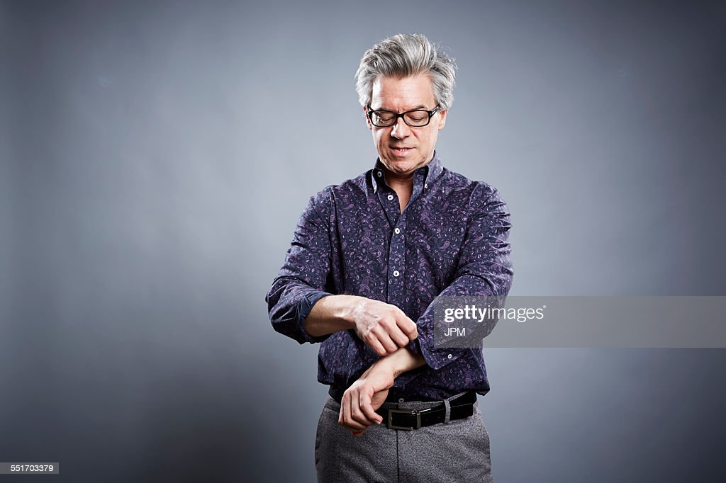 Studio portrait of mature businessman rolling up his sleeves : Stock Photo