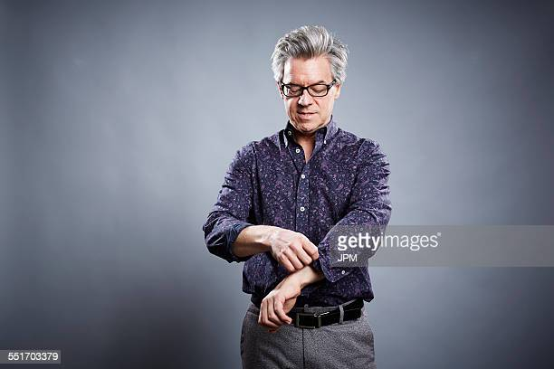 Studio portrait of mature businessman rolling up his sleeves