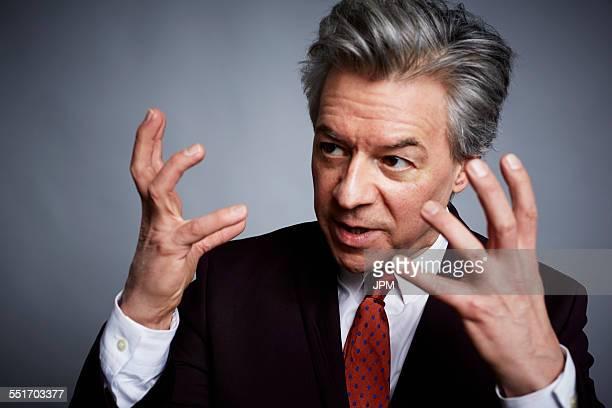 Studio portrait of mature businessman with hands open in explanation