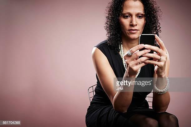 Studio portrait of mature businesswoman reading smartphone messages