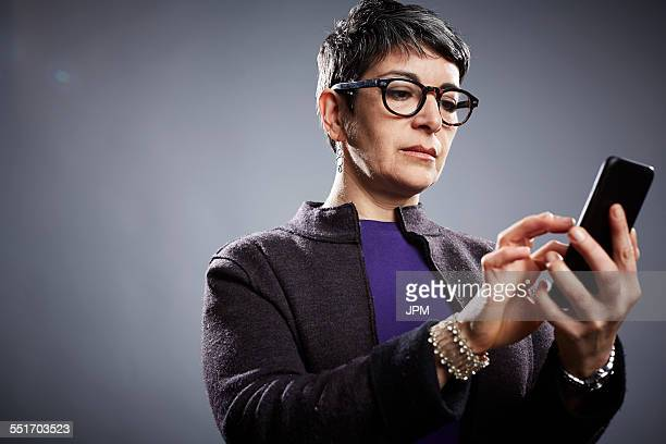 Studio portrait of mature businesswoman texting on smartphone