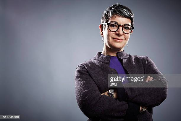 studio portrait of mature businesswoman with arms folded - physical position stock pictures, royalty-free photos & images