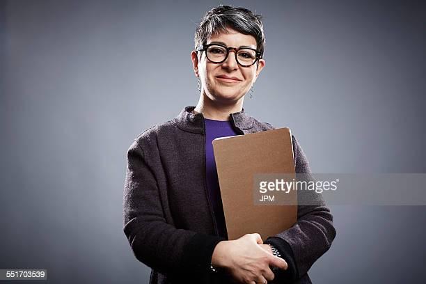 Studio portrait of mature businesswoman with clipboard