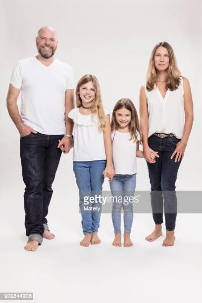 studio portrait of mature couple with two daughters, full length - vier personen stockfoto's en -beelden