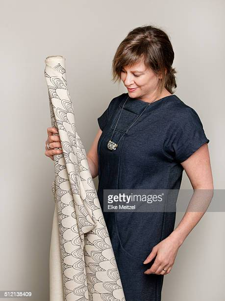 Studio portrait of mature female fashion designer holding up a roll of textile