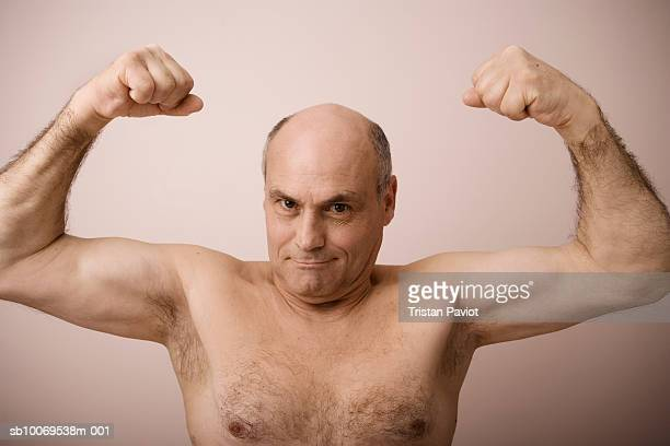 Studio portrait of mature man flexing muscles