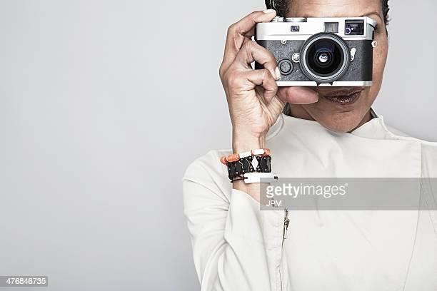 Studio portrait of mature woman holding up camera